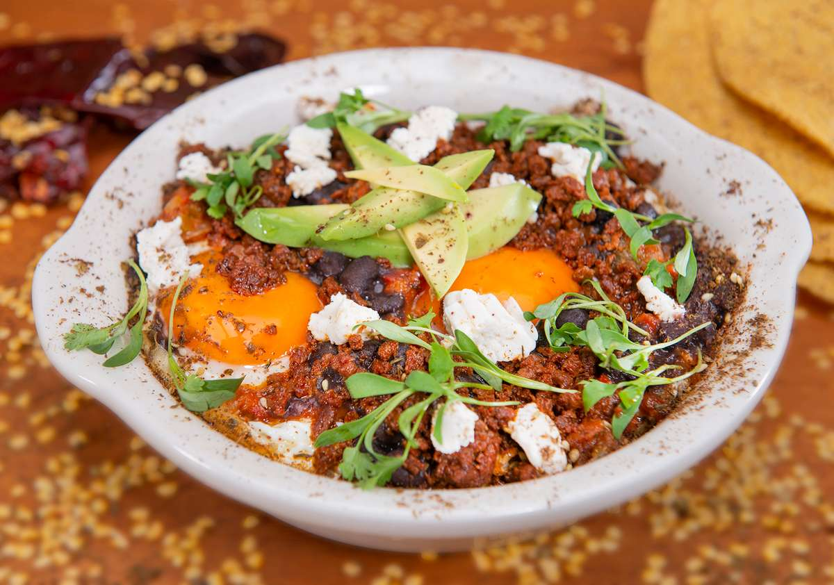 Huevos Rancheros in white bowl with eggs, beans and soy chorizo topped with almond cheese, ripe avocado and micro cilantro.