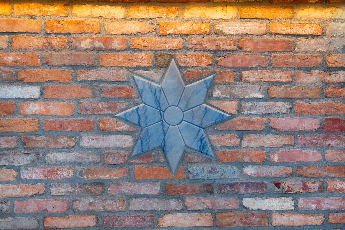 Blue marble seven-pointed star is embedded in a used brick wall
