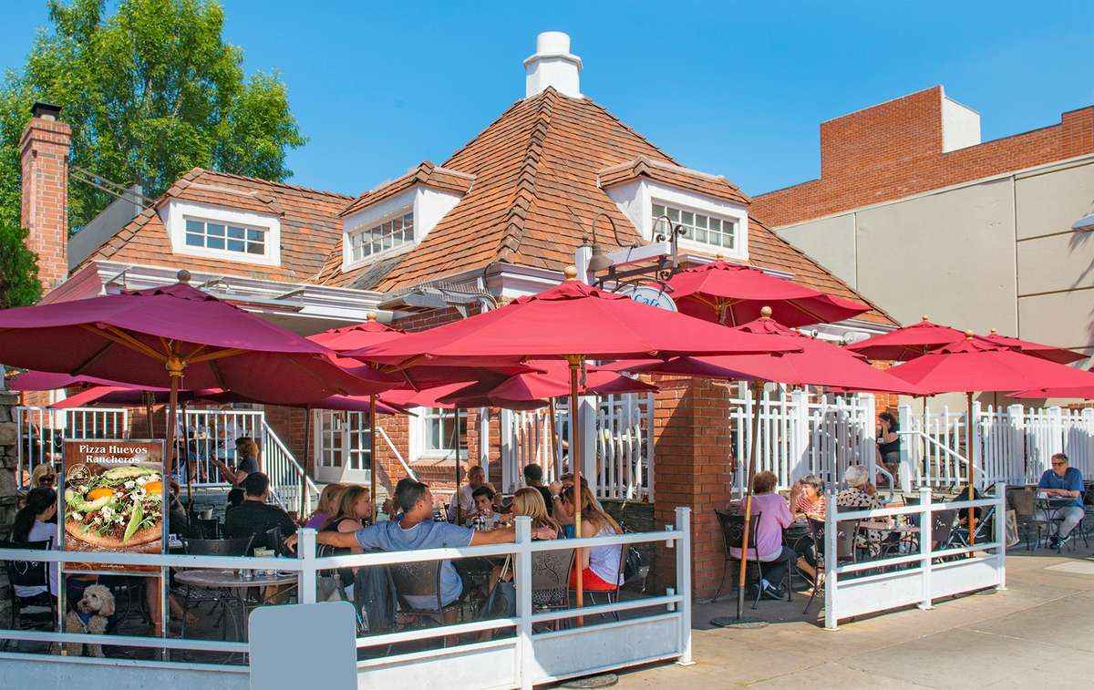 Exterior view of Urth Caffe Beverly Hills showing patio with guests sitting under red umbrellas