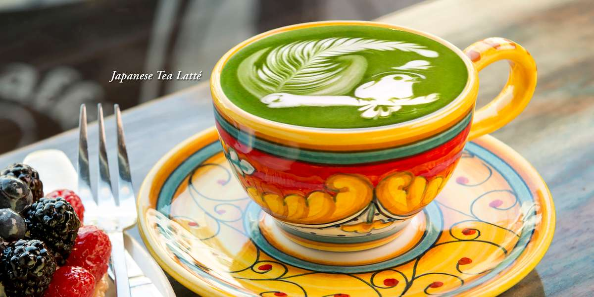 Decorative cup with Japanese Tea Latté with intricate green and white latté design is a perched songbird next to a fern.