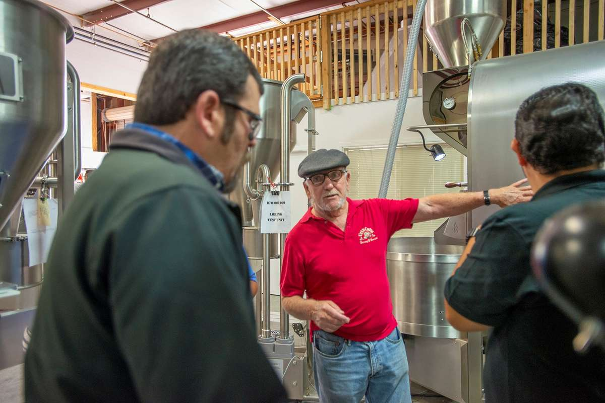 Urth senior coffee buyer Jan Eno wearing a red shirt at center at the Loring Factory, Santa Rosa, California.