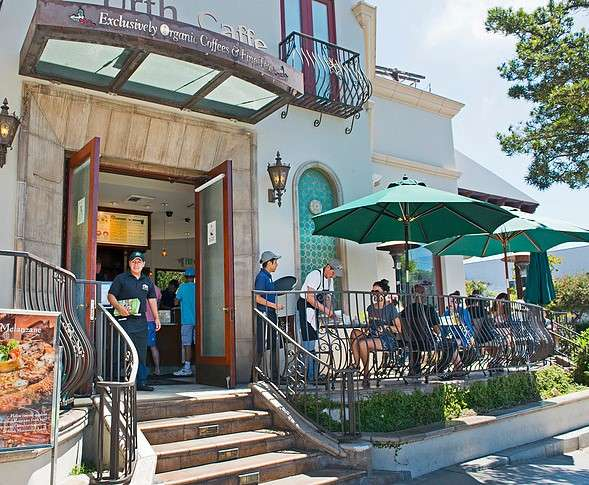 Day time view exterior of Urth Caffe Santa Monica patio with umbrellas, servers, guests