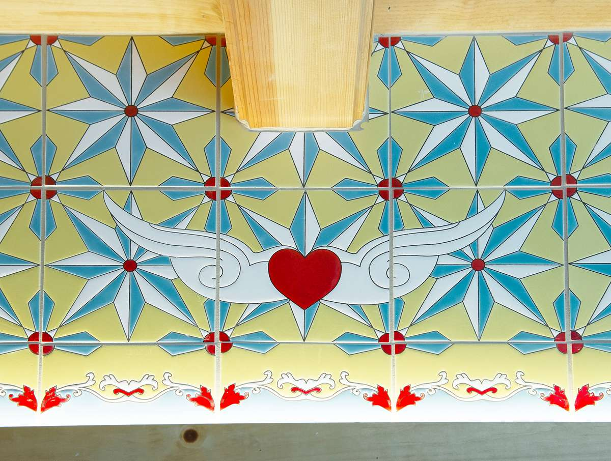 Tile motif shows a red heart with white wings with white, turquoise, light yellow, red accents.