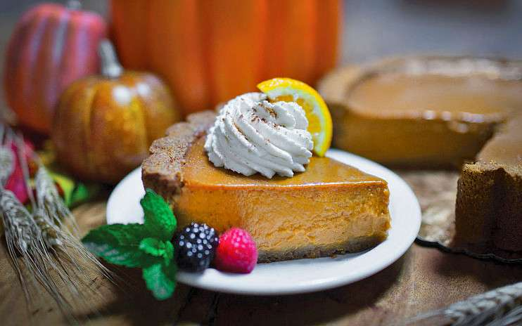 Slice of pumpkin pie with dollop of whipped crea,