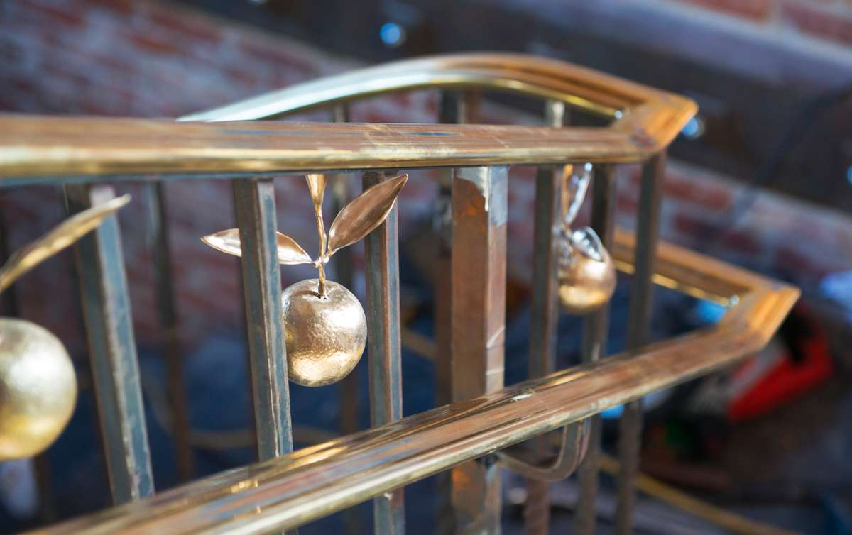 Finished iron stairway showing detail of golden oranges hanging from handrail.