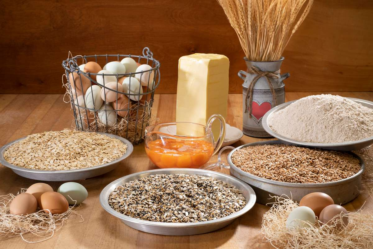 Bowls of whole grains, flour and fresh eggs and butter.
