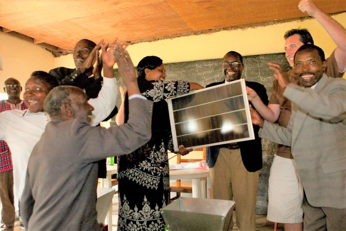 Urth Caffe coffee farmers are shown with solar panel that will power their farms in Nigeria