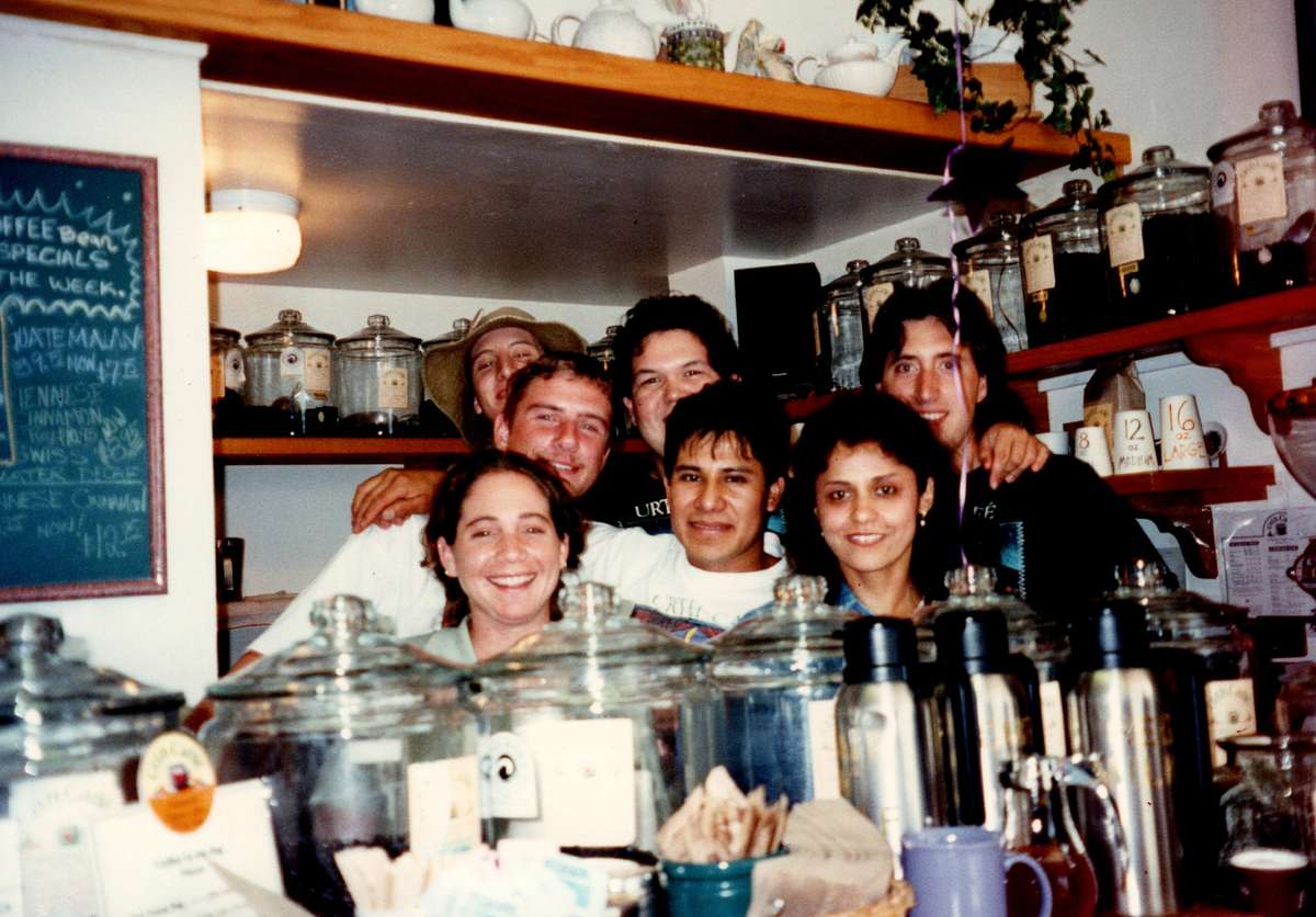 Group of 7 people behind coffee house counter with glass canisters on top of it.
