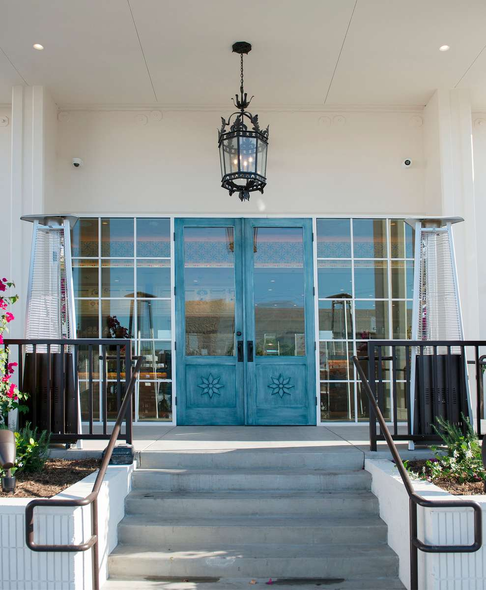 Entrance to Urth South Bay showing turquoise door, steps leading up to it, lighting fixture hanging above