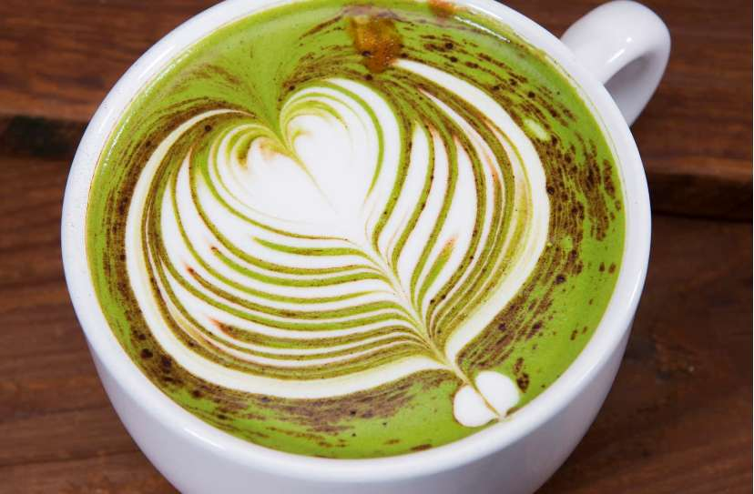 Rising Sun Matcha Latte with a detailed, layered heart design made from green tea, chocolate and milk in a white mug