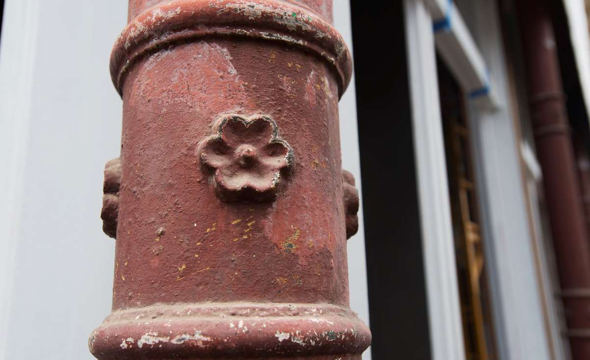 closeup of iron column from 1888 building - rusty, with flower motif