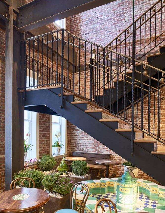Open iron stairs with decorative railing leading to upper floor