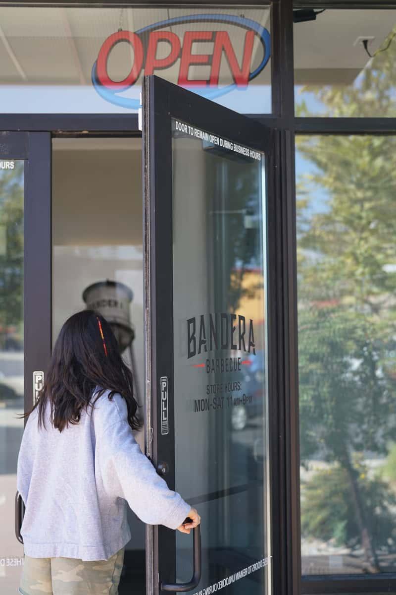 woman opening restaurant door
