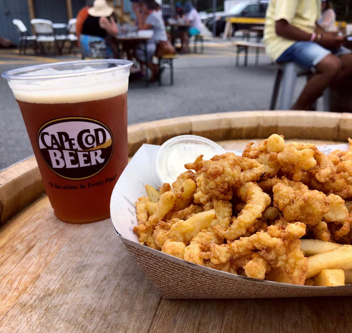 A basket of clam strips on a beer barrel with a pint of Cape Cod Beer