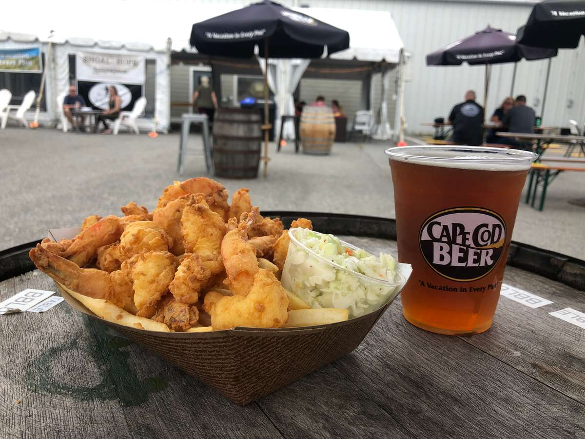 Basket of fried butterfly shrimp and fries with a pint of Cape Cod Beer, displayed on a beer barrel in the beer garden