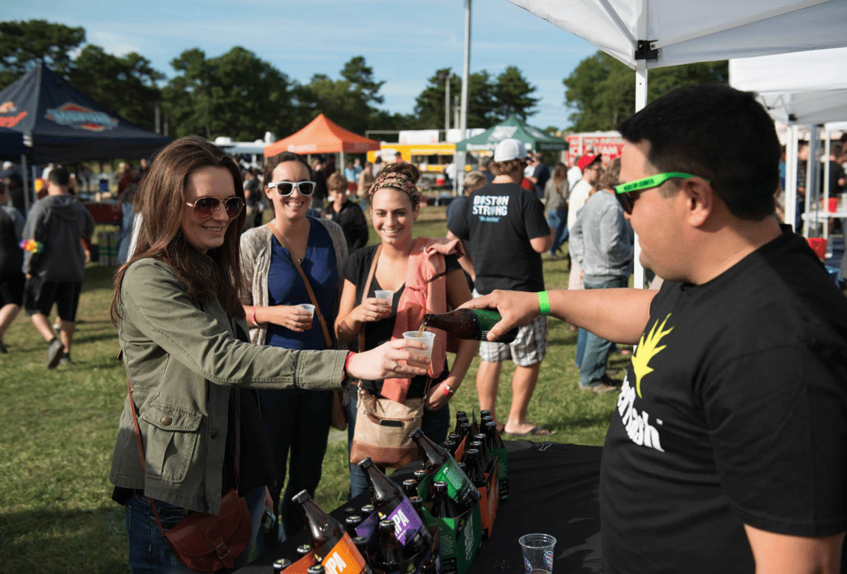 Vendor pours bottle of beer into cup for a woman in a beer tent