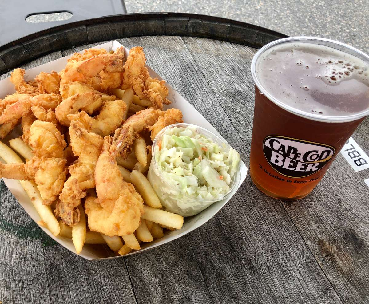 A basket of fried butterfly shrimp with a pint of Cape Cod Beer on a beer barrel