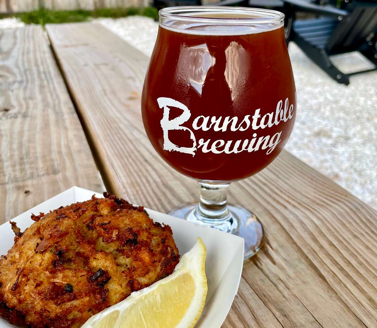 A stuffed quahog from the food truck with a glass of Barnstable Brewing's pumpkin beer on a picnic table.