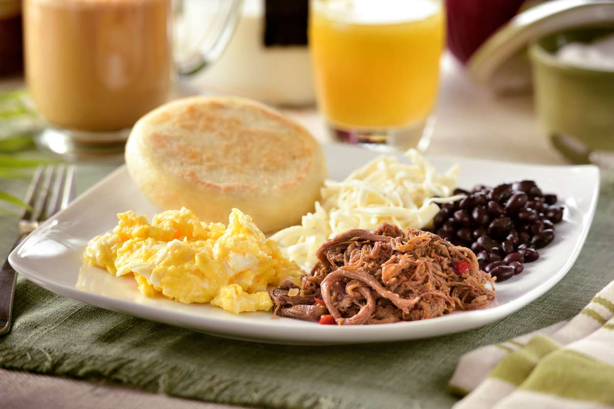 Latin Breakfast eggs, Meat, Black Beans, White Cheese and arepa with Latte