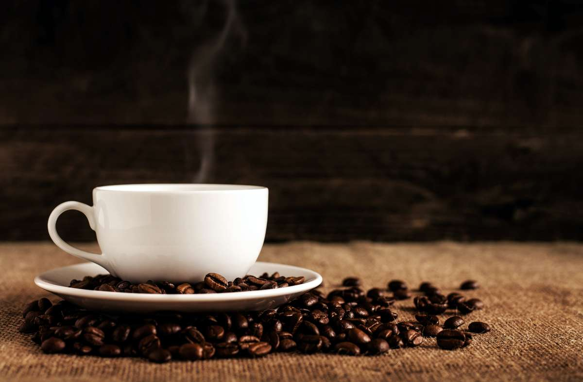 coffee cup on table with coffee beans
