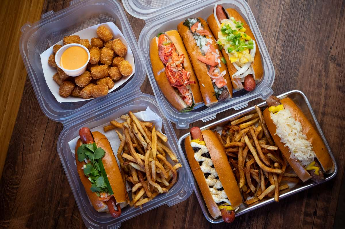 Hot dogs, fries, and tater tots in to go containers