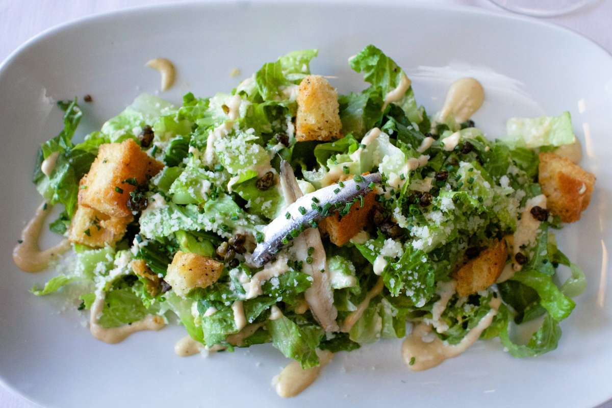 Overhead close up of a green caesar salad with croutons