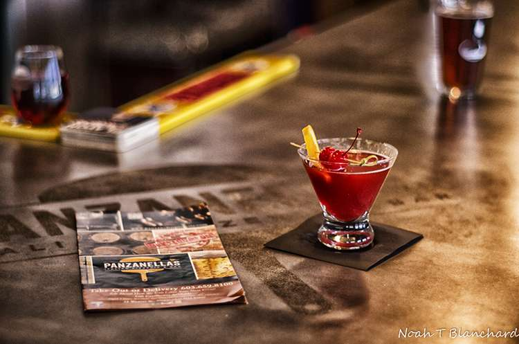 Image of a drink sitting on a bar next to a menu