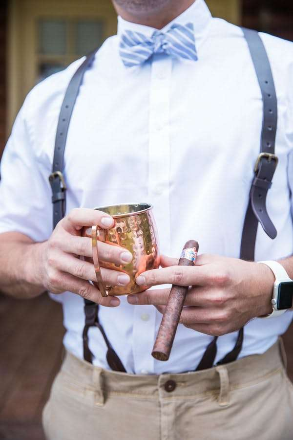 groomsman holding cup and a cigar