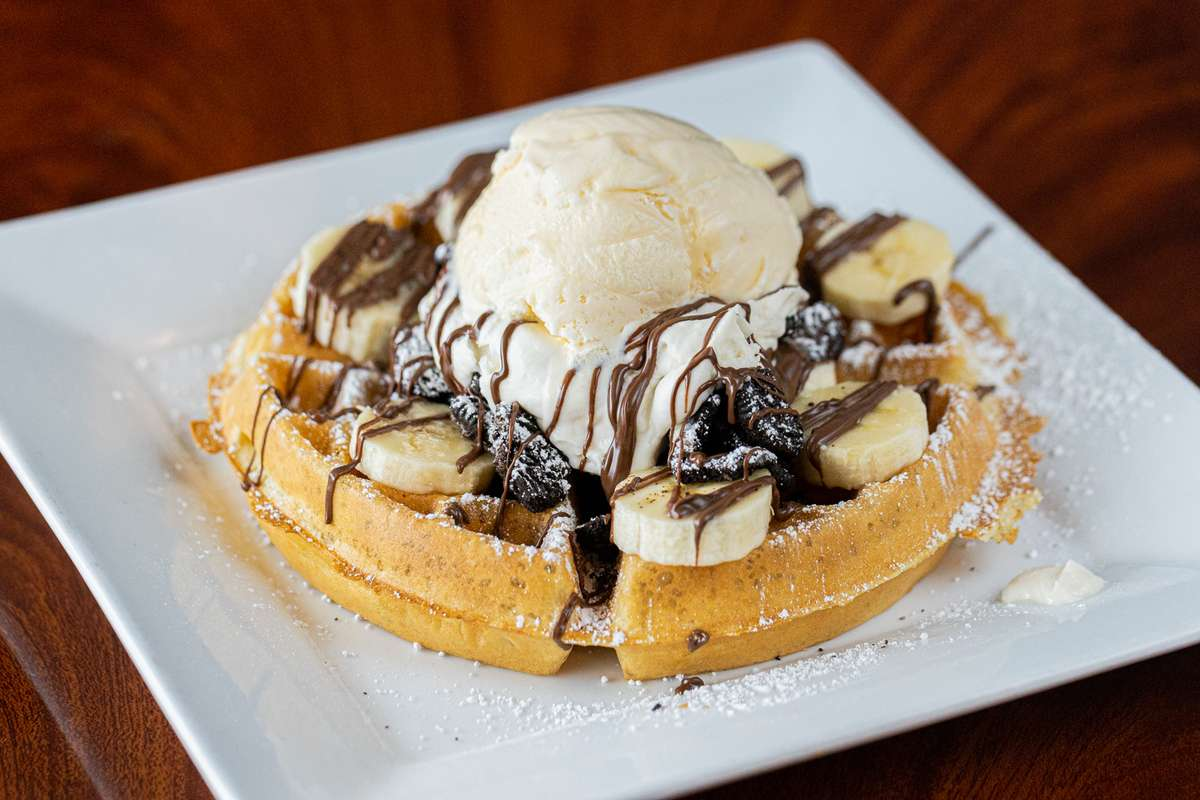 waffle topped with chocolate drizzle, bananas, and creme