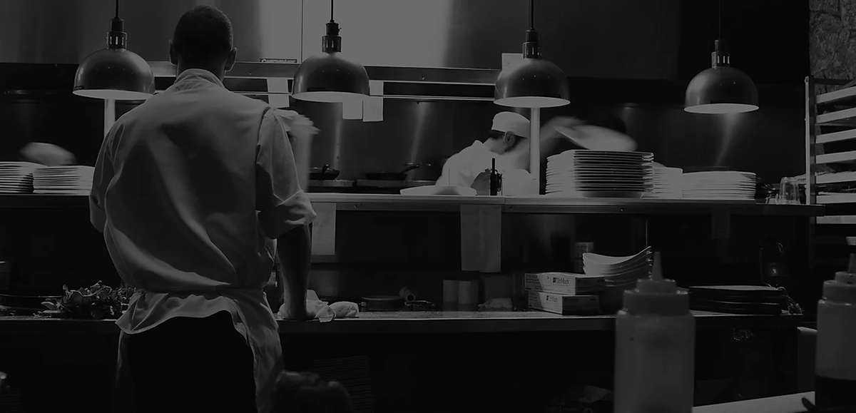 Black and white image of cook staff at mad chef kitchen & bar working in the kitchen