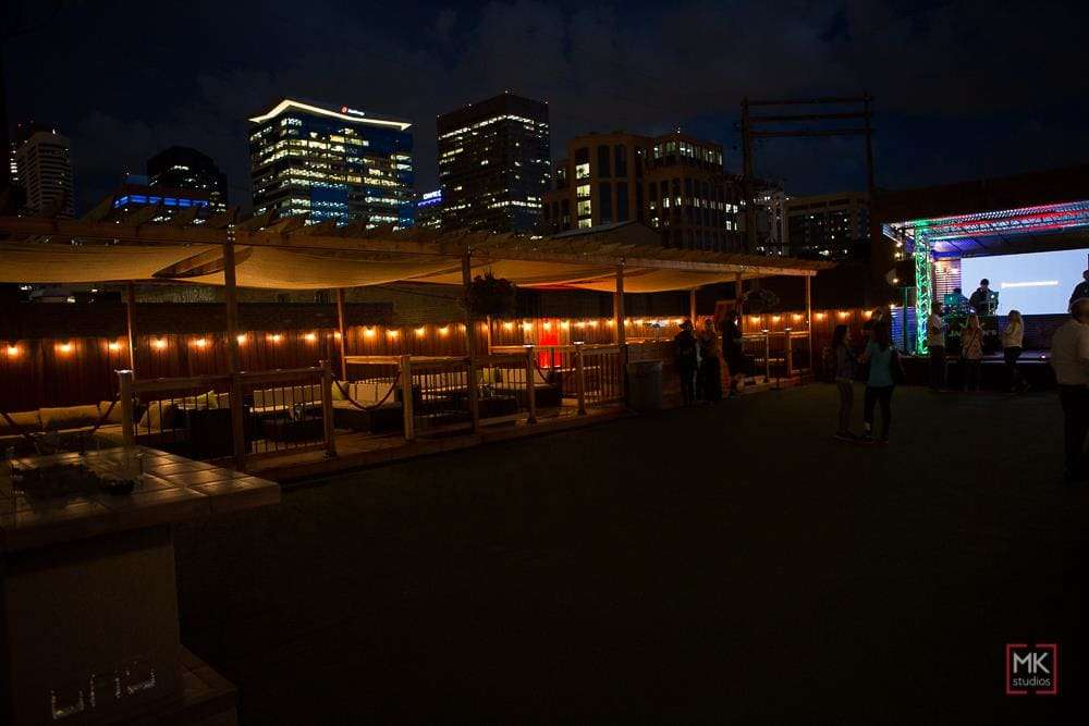 rooftop patio in front of a nighttime city landscape