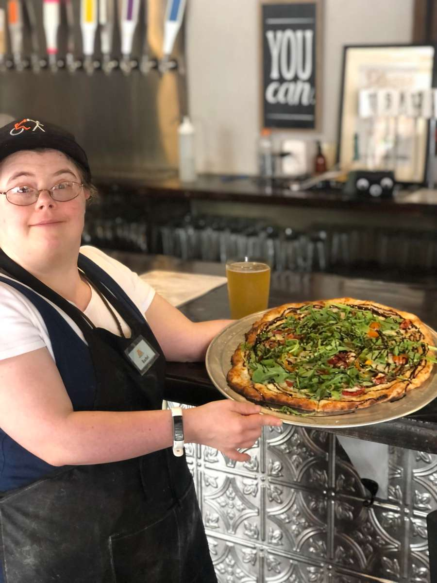 A woman with down syndrome is holding a pizza.