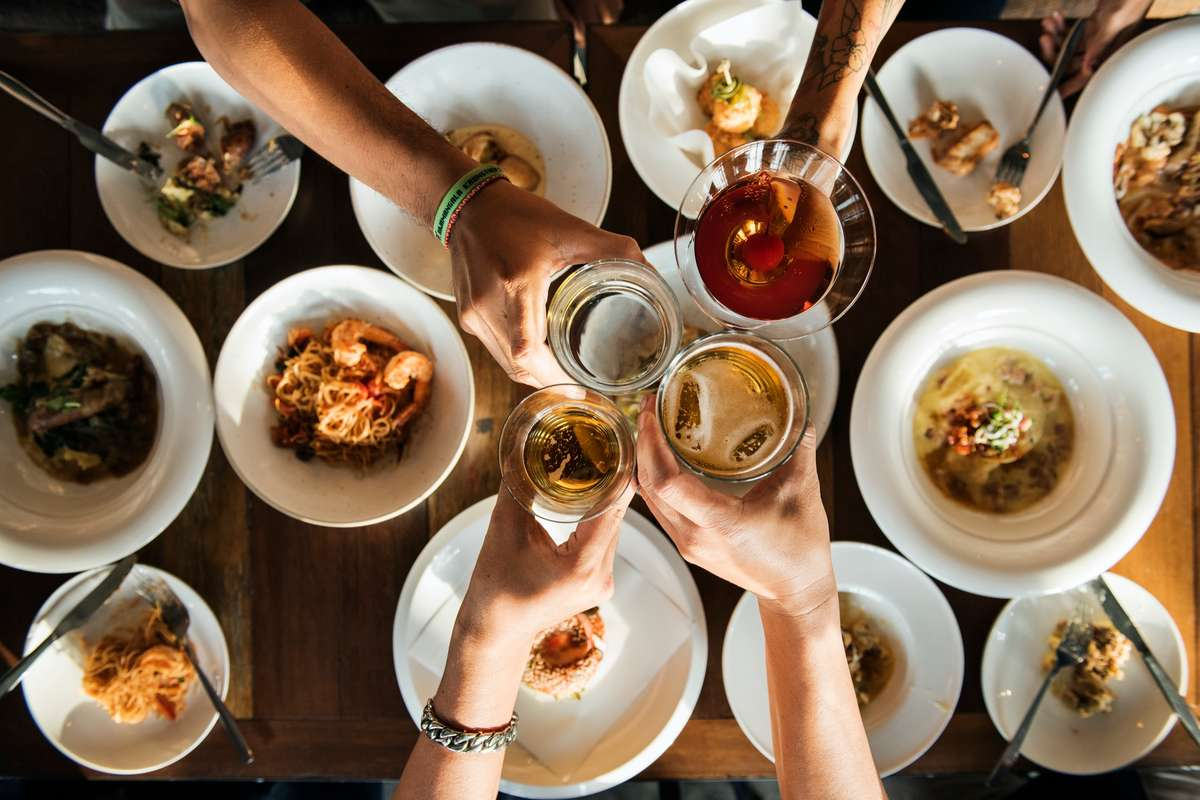 Group toasting with various drinks over a table covered in a variety of meals