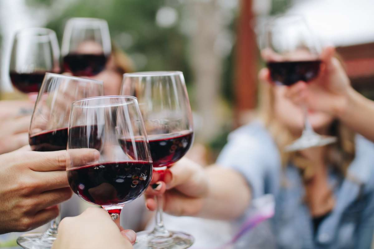 Group toasting with red wine