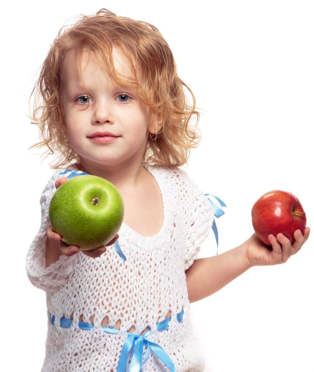 child holding two apples out as if offering them to someone