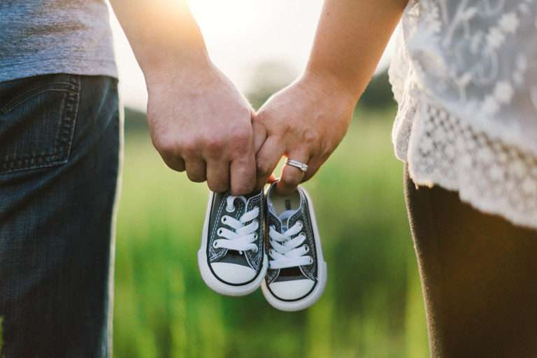 Couple holding baby shoes