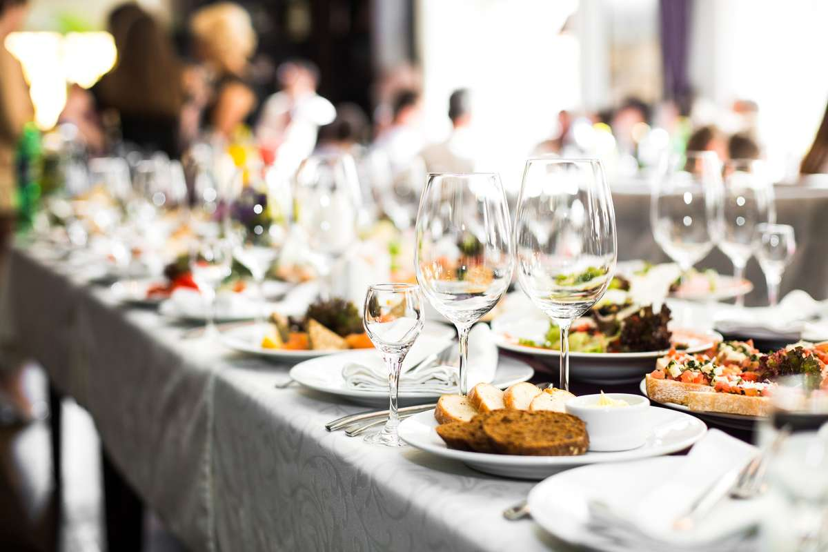Large party dinner table with wine glasses and meals