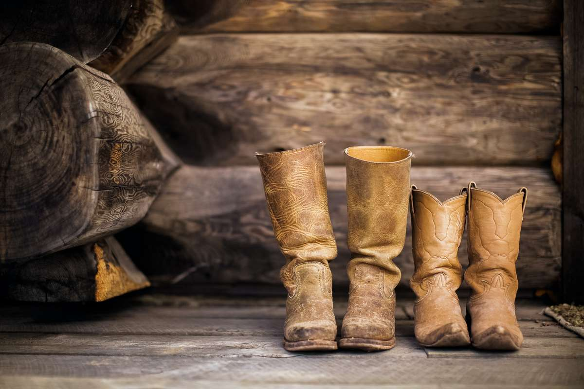 Well used tan colored cowboy boots sitting on weathered wood