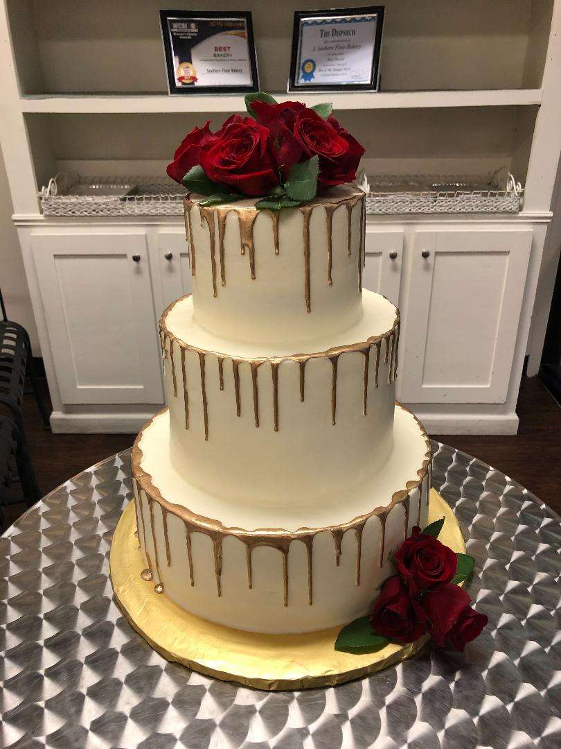 wedding cake with gold drip and roses