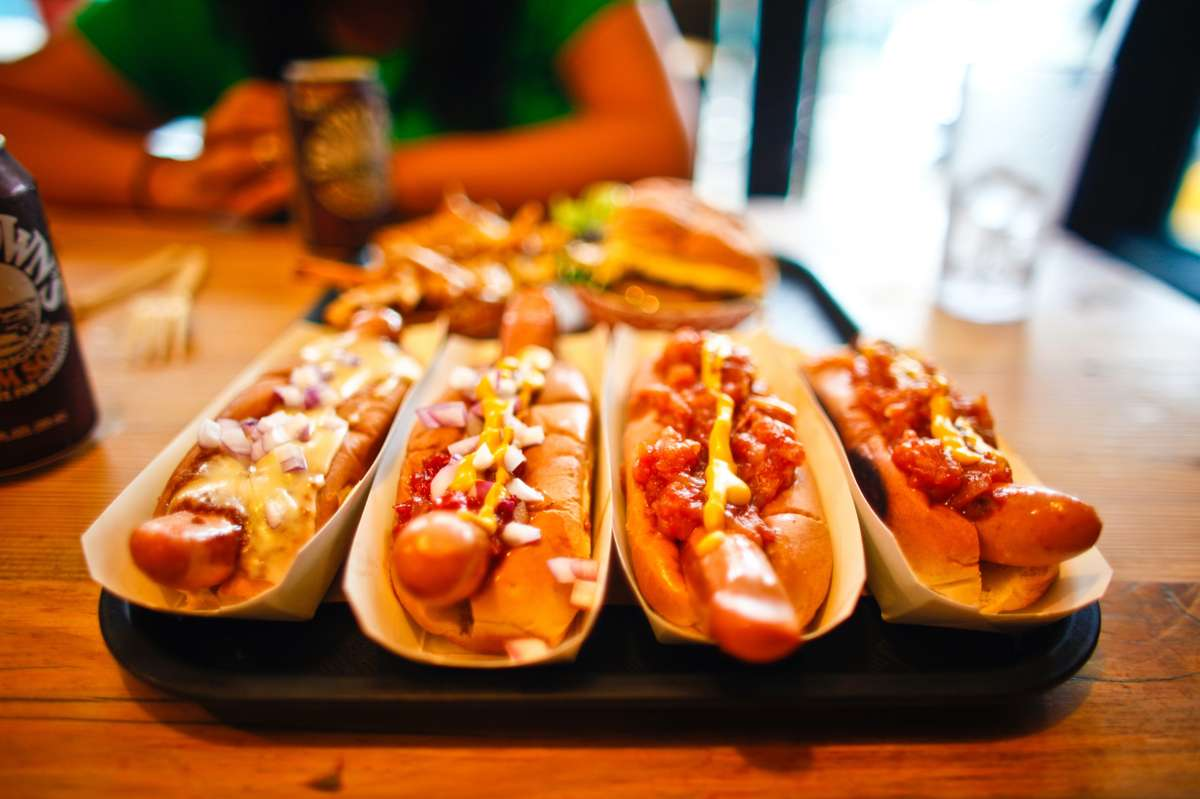 Multiple hot dogs with various condiments