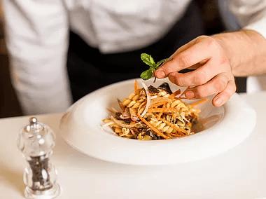 chef placing greens on dish