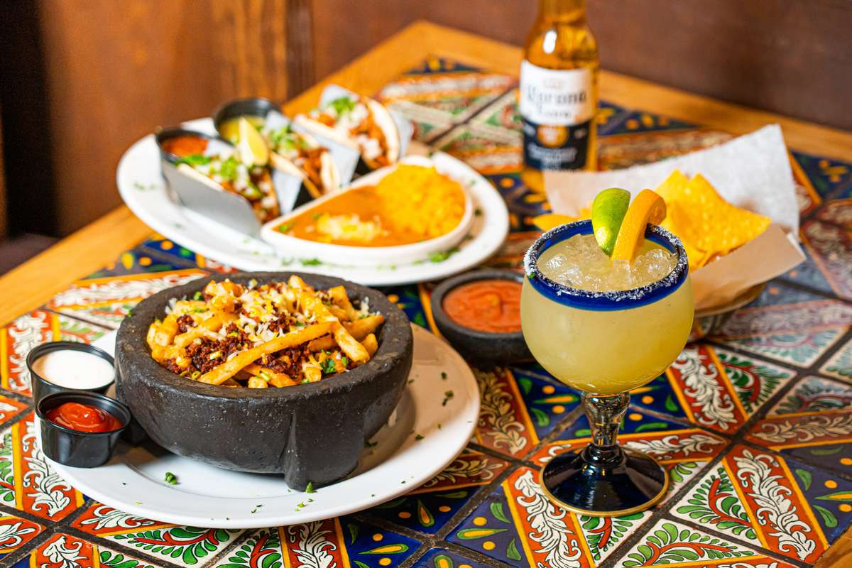 Different Mexican dishes with a margarita and beer