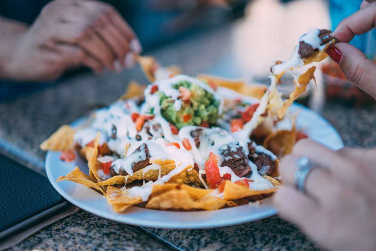people sharing a plate of nachos
