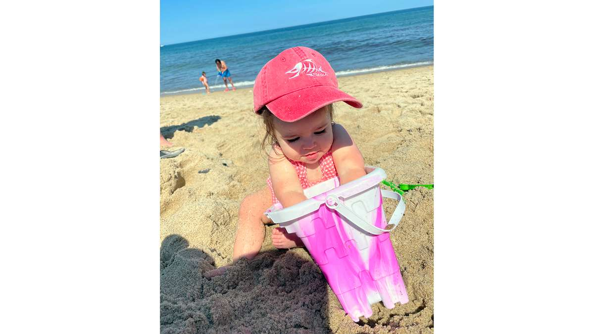 Little girl in Fish Tale Hat with sand Bucket
