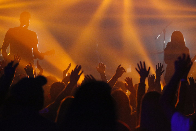people raising hands at music venue