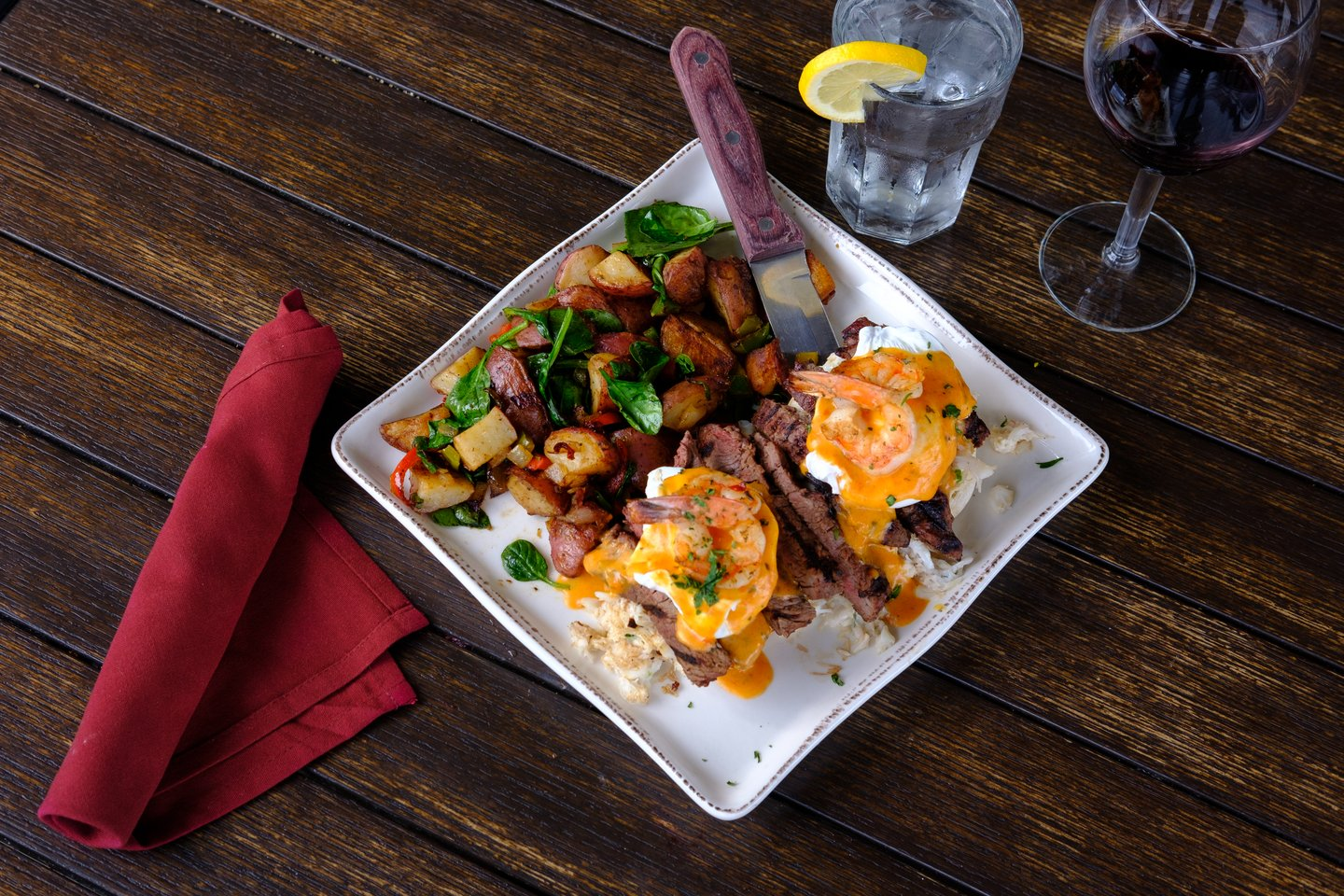overhead shot of eggs benedict and diced potatoes
