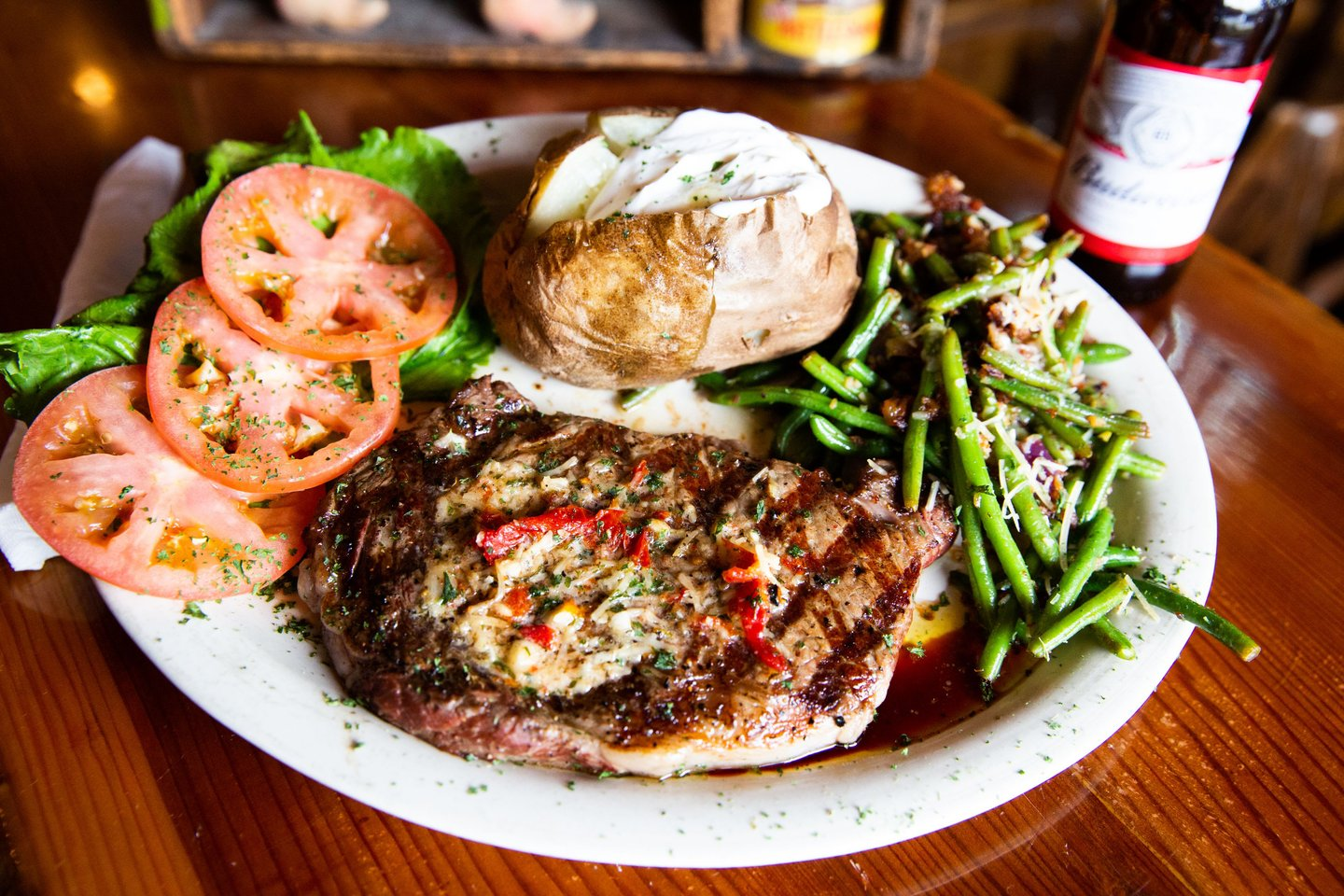 steak with baked potato and greenes