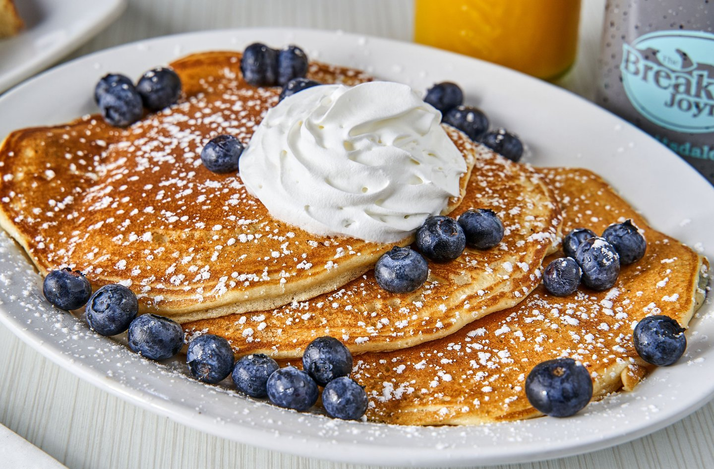 three pancakes topped with blueberries and whipped cream