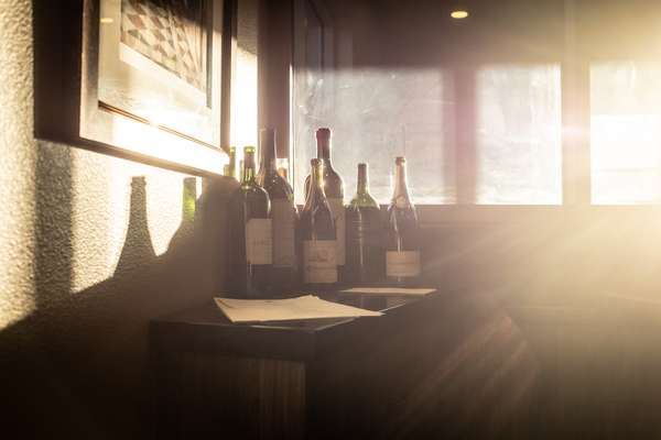 Wine bottle sitting on a table with the sun shining through a window.