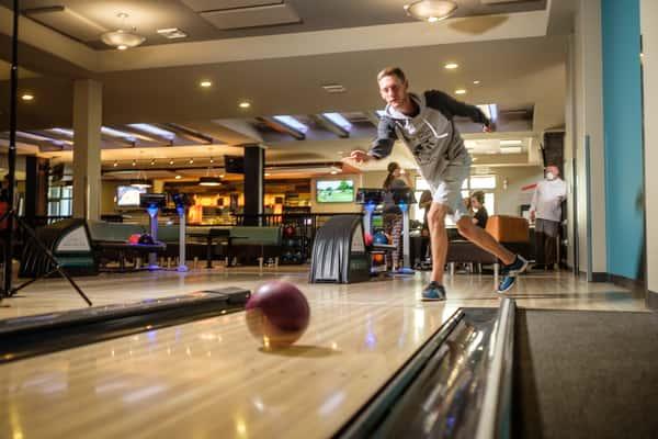 Kid throwing a bowling ball down a lane
